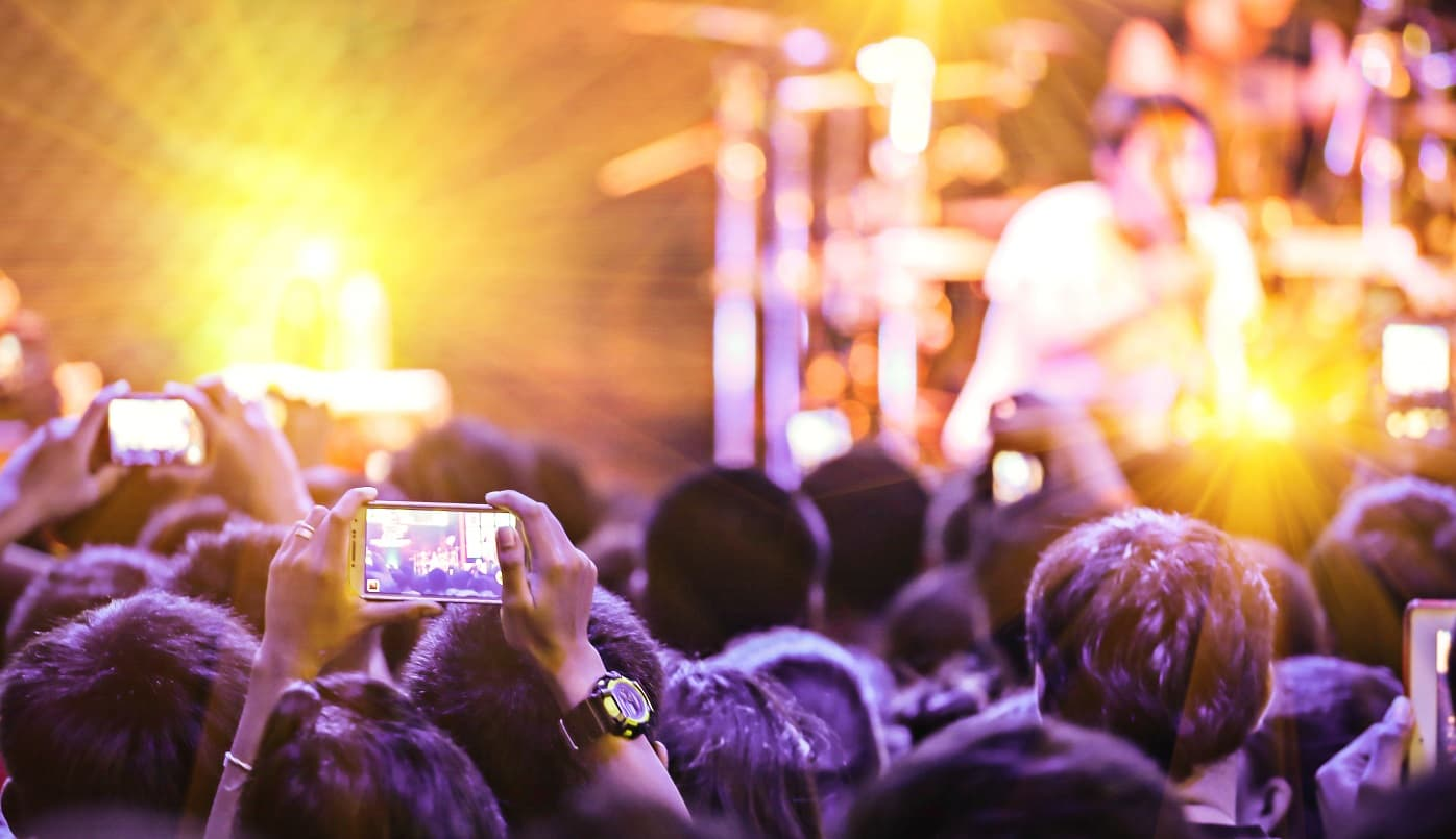 Event goers film a performance on their mobile phones.